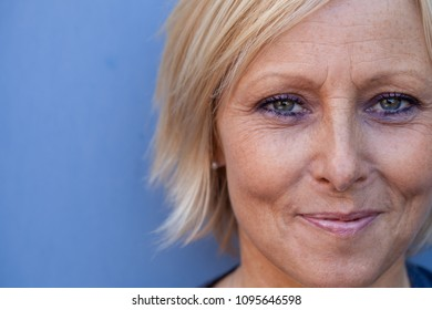 Close up of a healthy looking, smiling, Swedish, middle aged woman against a blue background.