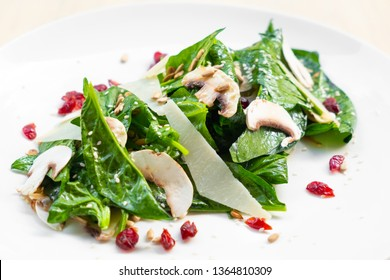 close up of a healthy Spinach, champignon mushrooms , raspberry and parmesan cheese salad on a white plate , natural light , fresh  Italian appetiser starter, prepared by professional skilled chef