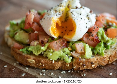 Close up of an healthy vegan vegetarian meal with chia and sesame seeds sprinkled over a runny poached egg, diced tomatoes and avocado on a cereal toasted bread slice, on a wooden plate.