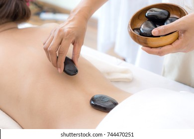 close up  healthy woman  during a back stone therapy massage in spa salon