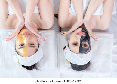 Close up of Healthy Young Woman getting mud Black and gold facial mask cosmetic procedure in the beauty salon.Skin treatment in spa salon concept.Top view