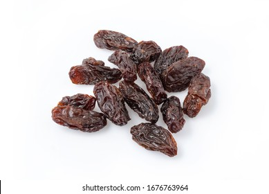 Close up of heap of dried raisins isolated on white background