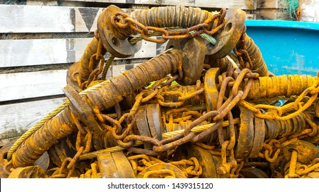 Close up of a heap of rusting and worn commercial sea fishing gear on the quayside of Mevagissey harbour. Cornwall. Landscape image with space for copy.