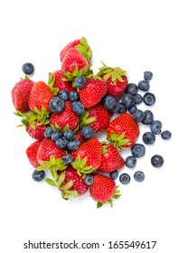 Close up of heap of strawberry and bilberry, isolated on white. Concept of healthy eating and dieting lifestyle