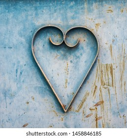 Close up of a heart shape graphic on the weathered and rusted metal door, painted in blue color.