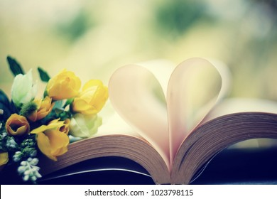 close up heart shape from  paper book and beautiful flower on old wood table, happy valentines day and spring season concept, process vintage tone