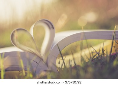 Close up heart shape from paper book on grass field with vintage filter
