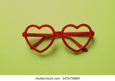 close up Heart-shaped sunglasses on a green background