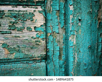 close up of heavily weathered pealing paint or wood door in aquamarine shades of blue