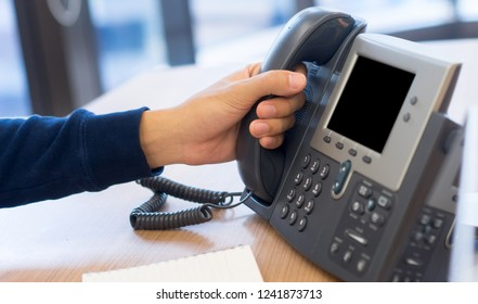 close up helpdesk employee man hand touching telephone handset for receiving incoming call at office table and typing on keyboard laptop for working another task , multitasking concept