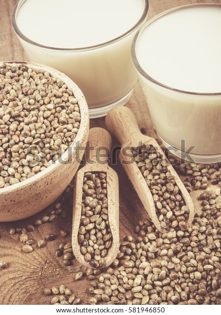 Close Up of hemp milk and seeds on wooden background .