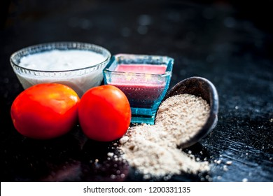 Close up of herbal and beneficial face pack for skin whitening i.e. tomato puree with yogurt and oats in a glass bowl with some raw tomatoes and yogurt on wooden surface.