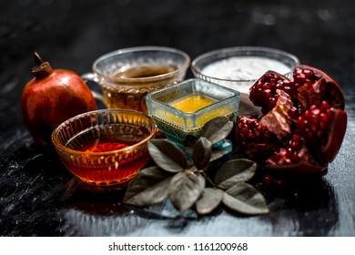 Close up of herbal and organic face pack of pomegranate with honey,green tea,curd or yogurt  on wooden surface in a bowl with some rose petals and leaves for Acne and pimples.