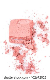 Close up High angle view of broken pink cosmetic powder with thick tipped brush against a white background