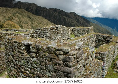 Close up high angle view of some of the preserved fortifications at high altitude along the Inca Trail in Peru of earlier Inca civilization with clouds below in the valley