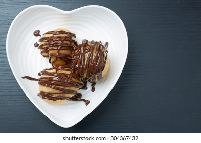 Close up High Angle View of Three Tasty Pastries with Chocolate Sauce on a White Heart Shaped Plate, Served on a Gray Table with Copy Space.