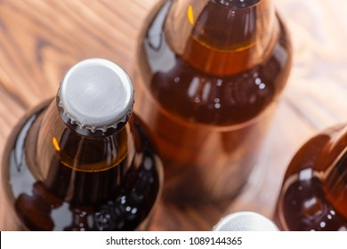 Close up high angle view of unlabelled bottles of craft beer with focus to the cap on a single bottle over a wood background