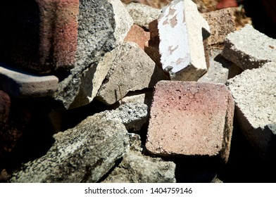 Close up high contrast image of discarded cement bricks and pavers in pile.