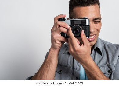 Close up high detailed portrait of man taking photo with vintage photocamera. Touristic concept image