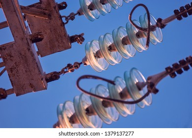 Close up of high voltage insulators at power-tower looking upwards from earth