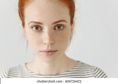 Close up highly-detailed portrait of amazing charming young European woman with ginger hair and perfect healthy freckled skin, wearing striped t-shirt, looking at camera with pretty cute smile - Shutterstock ID 604726421