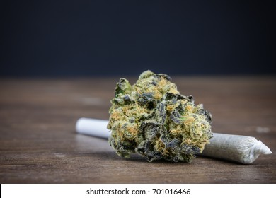 Close Up Of High-Quality Potent Marijuana Bud With Weed Joint On Wood Table With Dark Background. Selective Focus Macro Close Up With Copy Space.