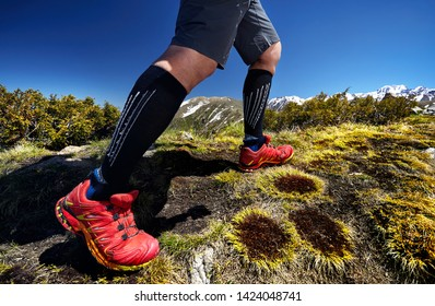 Close up of hiker legs in red shoes are climbing in the mountains at blue sky background. Healthy lifestyle. Outdoor travel concept.