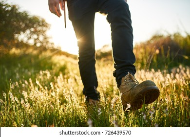 close up of hikers boot while walking through grass during hike