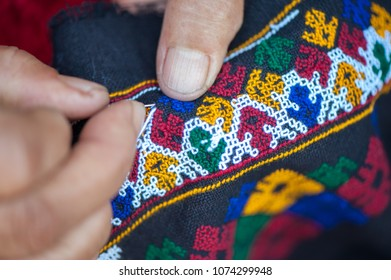 close up  hill tribe woman hand sewing the pattern on black fabric