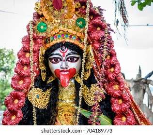 Close up of Hindu Goddess Kali decorated with ornaments and flowers .
