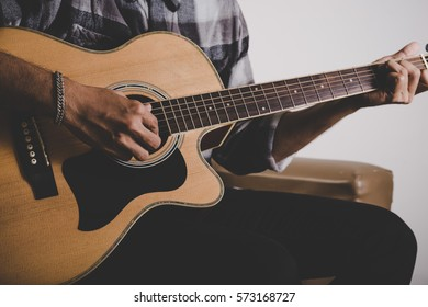 Close up of hipster beard man hand playing guitar.