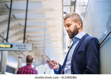 Close up of hipster businessman with smartphone, subway station