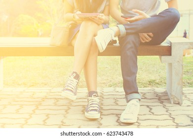 Close up of hipster couple in disinterest moment with smart phones in the outdoor, concept of relationship apathy, isolating using new technology and smartphone addiction in vintage with light shade