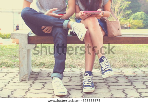 Close up of hipster couple in disinterest moment with smart phones in the outdoor, concept of relationship apathy and isolating using new technology and smartphone addiction
