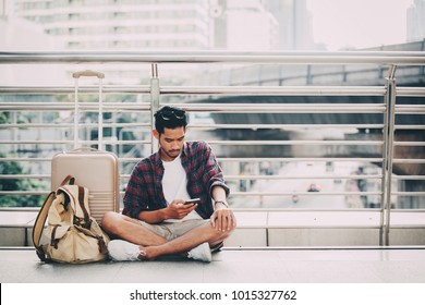 Close up of hipster traveller young man siting with backpack looking at smarphone