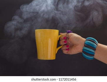 close up of hipster young woman hand handle  with Steaming of yellow coffee mug in the morning ,dark background