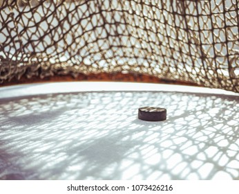 close up hockey goal puck in the net score