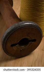 Close up of the hole of an empty wooden thread spool beside a spool of yellow thread.
