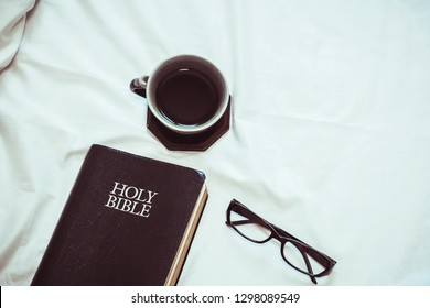Close up of holy bible with a cup of black coffee  and eyeglasses on bed in morning devotion time, christian background , copy space