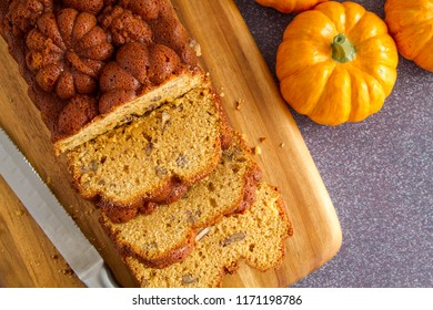 Close up of home baked loaf of pumpkin bread sitting on wooden cutting board with knife shot from above
