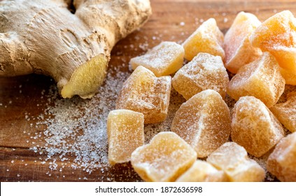 Close up of home made ginger candies and fresh ginger with sugar on wooden table.