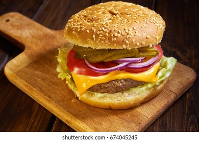 Close up of home made hamburger in rustic style on wooden background