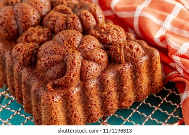 Close up of home made loaf of pecan pumpkin bread baked in decorative fall themed pan sitting on copper cooling rack on blue wooden table