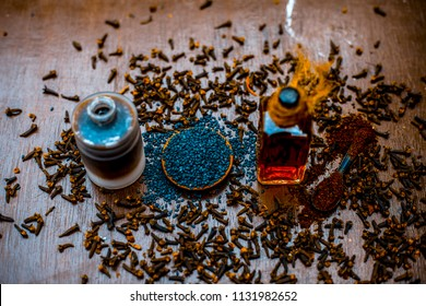 Close up of home remedy for earache i.e. Black sesame seeds oil with clove oil. Raw black sesame seeds and cloves on wooden surface.
