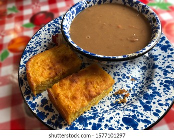 Close up of home-cooked beans and cornbread served on a spotted blue tin plates