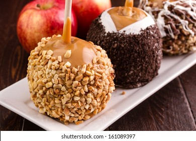Close up of homemade caramel apple decorated with peanuts on rectangular white plate