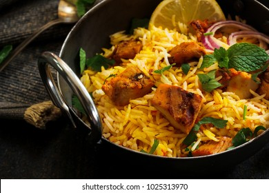 Close up of Homemade Chicken Tikka Biryani served with Raita on dark moody background, selective focus