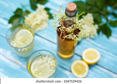 Close up of homemade elderflower syrup in a bottle with elderflowers