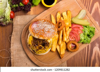 Close up Homemade grilled cheeseburger with fried caramelized onion and melting cheddar cheese serving with finger fries , onion rings , tomato and pickles on wood background. Top view.