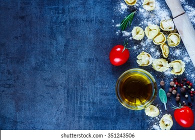 Close up of homemade Italian pasta tortellini, tomatoes, flour, fresh herbs, spices and olive oil on dark vintage background with space for text. Healthy eating or cooking concept.